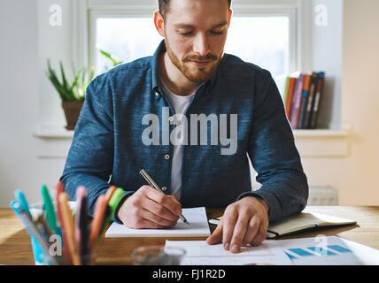 Seul homme barbu en chemise bleue avec le bloc-notes et stylo contrôle de documents pour comparer ou enregistrer Banque D'Images