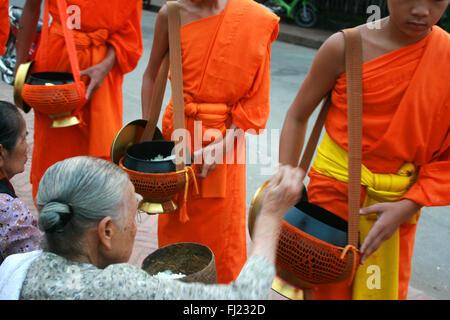 Tak bat - rituel des moines bouddhistes recevoir le riz et de la nourriture de pupulation tôt le matin à Luang Prabang, Banque D'Images