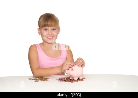 Smiling girl putting coins in piggy bank isolé sur la table Banque D'Images