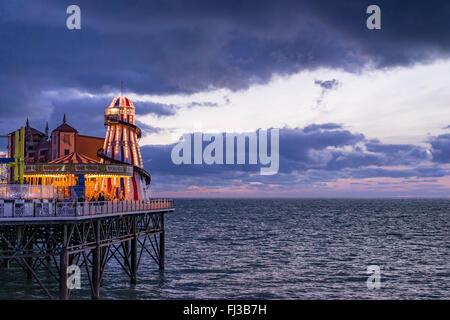 Une vue de la rive de la mer et de l'attraction à l'extrémité de la jetée de Brighton Palace prises au crépuscule Banque D'Images