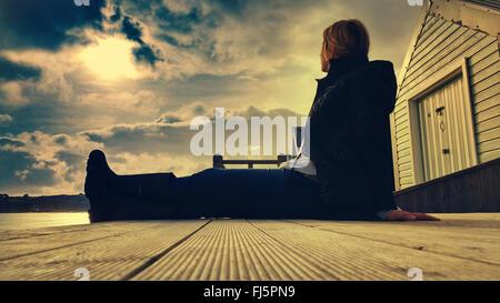 Jeune femme assise confortablement sur plancher cabine de plage en bois Banque D'Images
