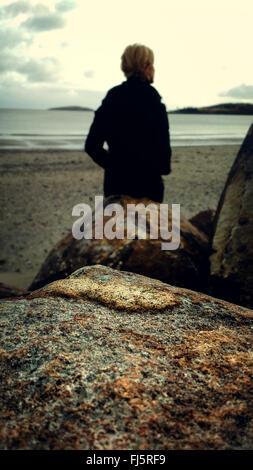 Jeune femme sur la plage par les roches Banque D'Images