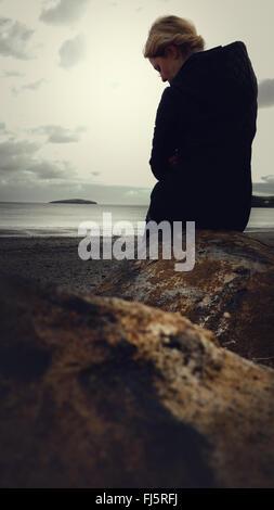 Femme debout sur la plage par la roche Banque D'Images