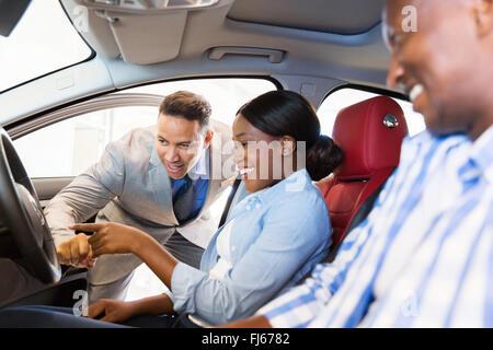 Vendeur montrant nouvelle voiture à African couple in showroom Banque D'Images