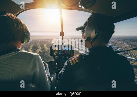 Vue intérieure d'un hélicoptère en vol, avec l'homme et de la femme pilote un hélicoptère sur une journée ensoleillée. Banque D'Images