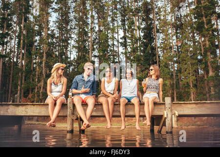 Portrait of young friends sitting on jetty et parler. Les jeunes, hommes et femmes, profiter d'une journée au bord Banque D'Images
