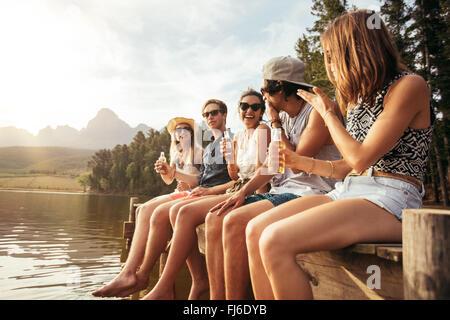 Portrait of happy young friends sitting on pier au lac, boire des bières. Les jeunes hommes et femmes passer une Banque D'Images
