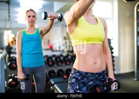 Mettre en place deux femmes dans l'élaboration d'une salle de sport avec des poids Banque D'Images
