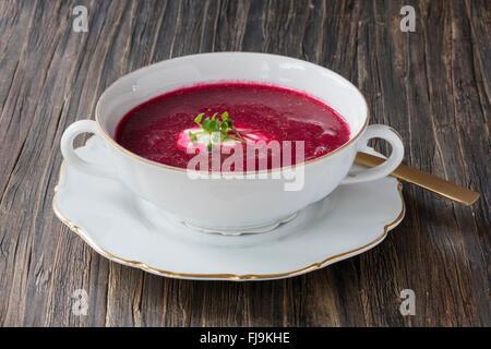 Délicieux produits biologiques soupe de betteraves dans un bol blanc sur une surface en bois foncé Banque D'Images