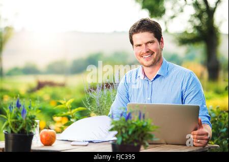 Ordinateur portable avec jardinier, assis à la table, nature vert Banque D'Images