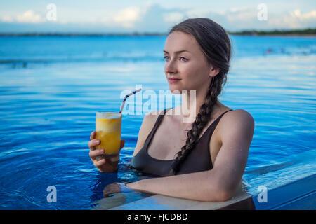 Jeune femme en prenant un verre dans la piscine au coucher du soleil Banque D'Images