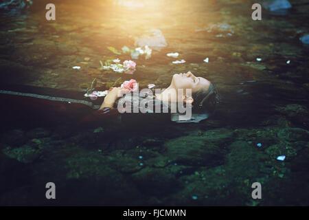 Femme morte flottant dans la rivière sombre . Conceptuel Ophelia Banque D'Images