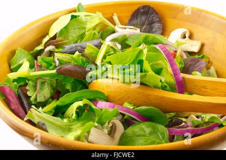 Mesclun bio salade de champignons et servi dans un bol en bois, sur fond blanc Banque D'Images