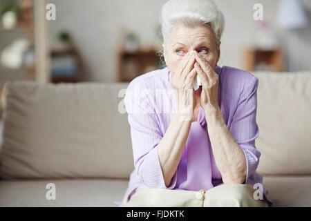 Sad senior woman sitting on sofa et pleurer Banque D'Images