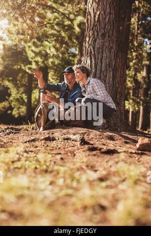 Senior couple randonnées dans la nature avec l'homme tenant un compas et indiquant la direction de la femme. Couple Banque D'Images