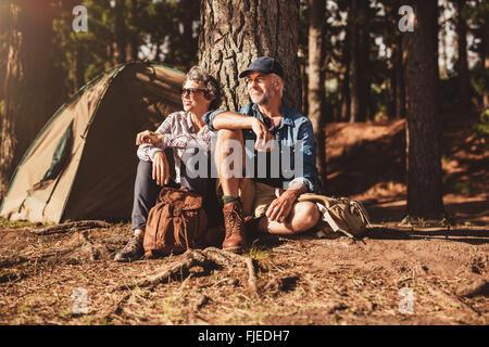 Portrait of senior couple sitting ensemble sous un arbre dans la forêt et à la recherche à une vue. Man and Woman Banque D'Images