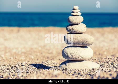 L'équilibre des pierres, vintage retro hiérarchie comme instagram pile dans la mer bleu fond. Spa ou bien-être, Banque D'Images