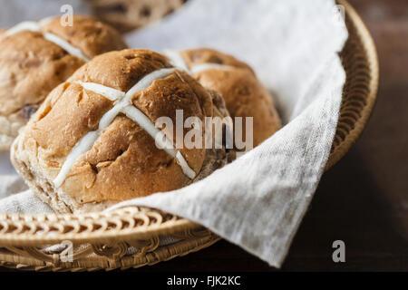 Trois brioches de Pâques dans un panier sur une table en bois rustique Banque D'Images