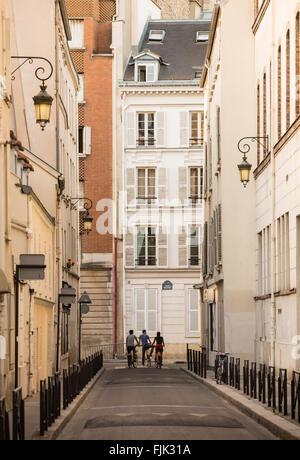 Trois cyclistes pause à la fin d'une rue étroite à Paris, France Banque D'Images