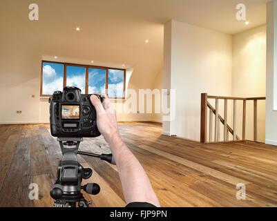 Mains tenant un appareil photo professionnel sur trépied, sur le point de prendre un coup d'un intérieur moderne Banque D'Images