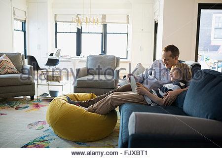 Père Fils sharing digital tablet salon canapé Banque D'Images