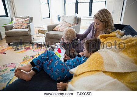 Mère et fils en pyjama using digital tablet Banque D'Images