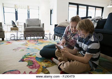 Brother and sister using digital tablet salle de séjour Banque D'Images