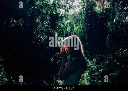 Vue latérale du jeune femme contre des arbres en forêt