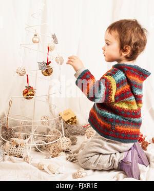 Garçon jouant avec décoration de Noël sur le lit chez lui Banque D'Images