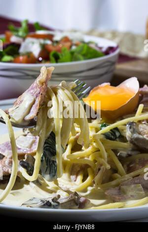Une macro image d'une assiette de spaghetti alla carbonara été taquiné avec une fourchette. Banque D'Images