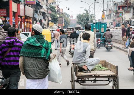 Scène de rue montrant les piétons et les diverses formes de transport y compris les pousse-pousse, des charrettes, Banque D'Images