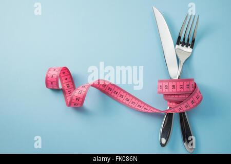 Fourchette et couteau enveloppé de ruban à mesurer sur fond bleu Banque D'Images