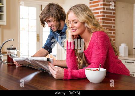 Cute couple lisant le journal Banque D'Images