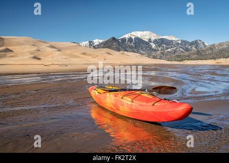 Dans les eaux peu profondes de kayak de Medano Creek avec beaucoup de dunes de sable et les montagnes Sangre de Cristo en arrière-plan