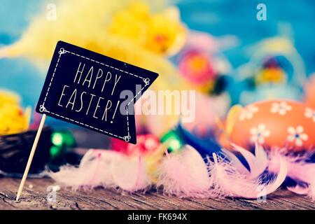 Libre d'une pancarte en forme de drapeau noir avec le texte joyeuses Pâques sur une surface en bois plein de plumes Banque D'Images