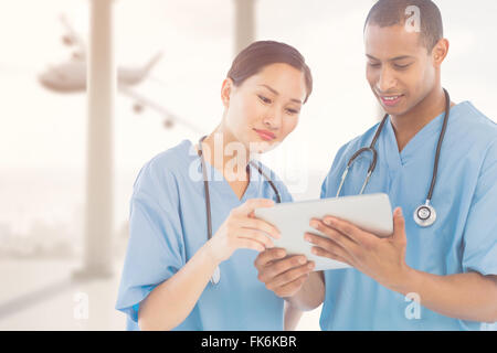 Image composite de chirurgiens looking at digital tablet in hospital Banque D'Images