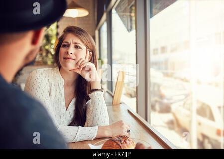 Belle jeune femme assise dans un café et en regardant son petit ami. Jeune couple du coffee shop. Banque D'Images