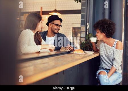 Heureux les jeunes gens assis dans un café et de parler les uns aux autres. Groupe de jeunes amis communiquer et Banque D'Images