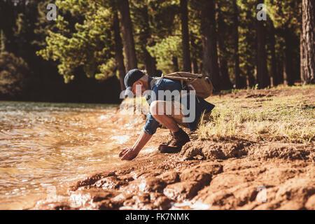 Side portrait of senior male hiker sitting by a lake et mettant les mains dans l'eau. Homme mûr lave-face dans le Banque D'Images