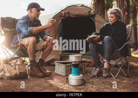 Couple assis à leur camping, avec l'homme de boire du café. Senior couple camping dans la nature. Banque D'Images