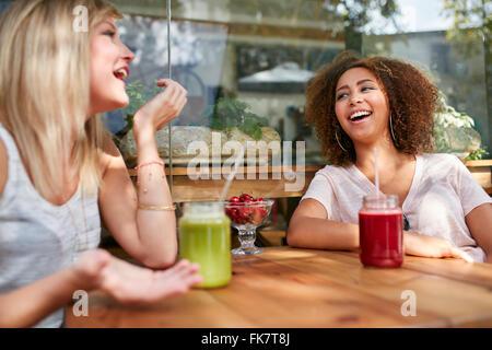 Deux femmes le commérage et souriant dans un restaurant. Jeunes amis assis à un café en plein air de s'amuser. Banque D'Images