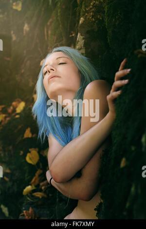 Femme belle et rayon de lumière dans le bois sombre. Embrasser la Nature Banque D'Images