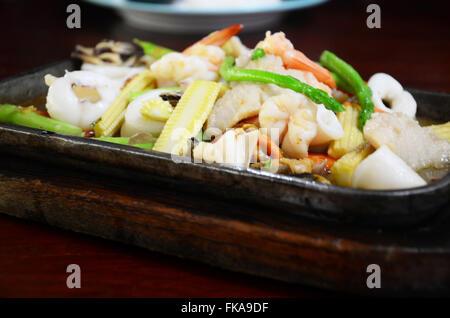 Sauté de légumes mélangés avec des fruits de mer en sauce aux huîtres servi sur la poêle chaude Banque D'Images