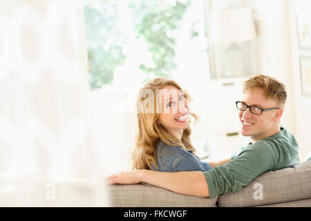 Portrait of young couple sitting on sofa Banque D'Images