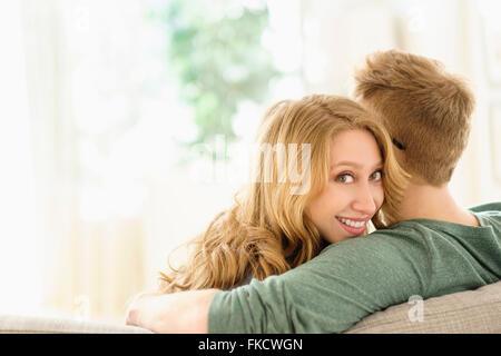 Portrait of young woman hugging boyfriend sur canapé Banque D'Images