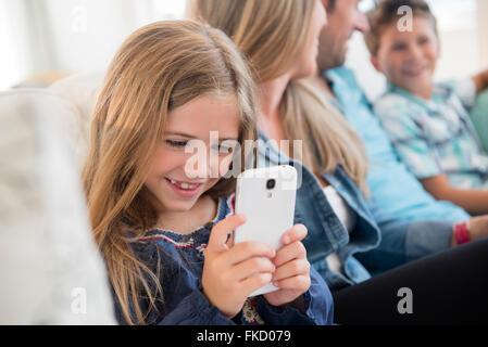 Girl (6-7) sitting on sofa, à l'aide de smart phone Banque D'Images