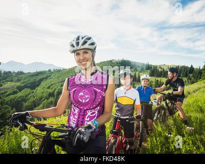 Les parents et les fils (10-11, 12-13) dans les montagnes avec des bicyclettes Banque D'Images