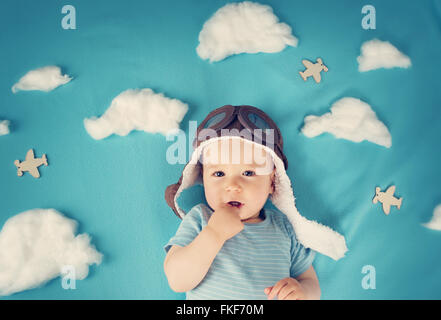 Boy lying on blanket with white clouds Banque D'Images