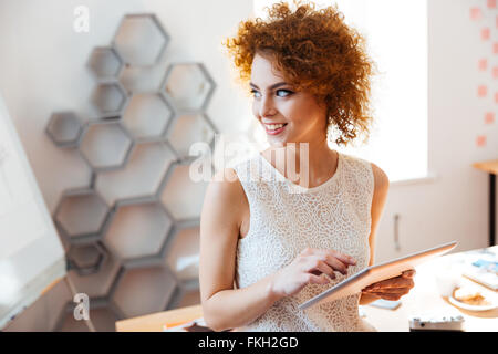 Cheerful curly cute young business woman standing et à l'aide de tablet in office