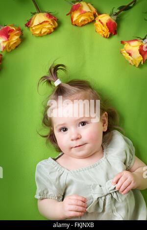 Jolie petite fille couchée sur une couverture verte avec des roses jaunes Banque D'Images